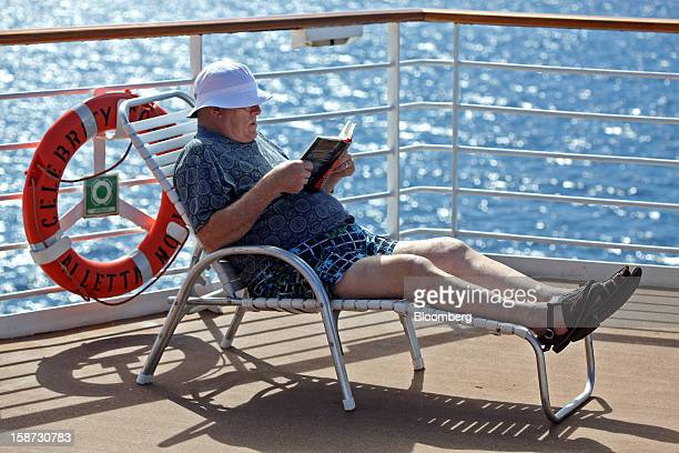 A passenger reads a book aboard Celebrity Cruises Inc's Constellation cruise ship in the Caribbean Sea near the coast of Cuba on Sunday Dec 16 2012...