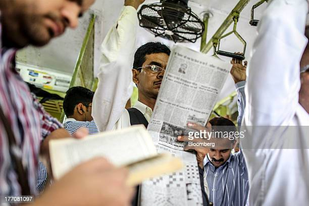 A passenger reads a newspaper as he rides on a train during the morning rush hour in Mumbai India on Tuesday Aug 20 2013 Indias biggest stockmarket...