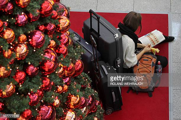 A passenger reads next to a Christmas tree as she waits for a plane at the airport in the western German city of Duesseldorf on December 24 2010...