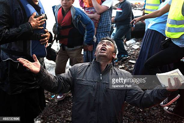 A passenger rejoices after a boat carrying a group of migrants arrives from Turkey onto the island of Lesbos on October 18 2015 in Sikaminias Greece...