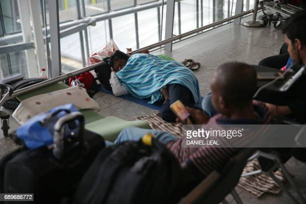 A passenger rests on the floor of Terminal 5 of London's Heathrow Airport on May 29 2017 Passengers faced a third day of disruption at Heathrow...