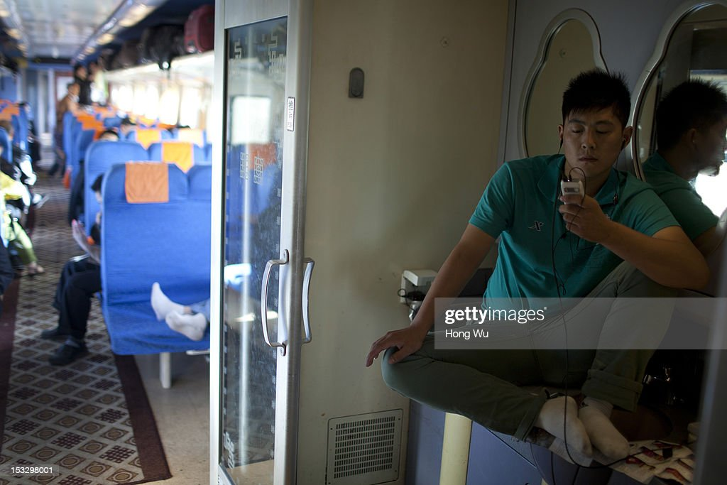 Passenger rests on wash basin in a train carriage of from Beijing to Lhasa on August 15, 2012 in Delingha, China. After Qinghai-Tibet Railway went into operation on July 1, 2006, connecting China's capital Beijing and Lhasa of Tibet Autonomous Region by 4,064 km of railway line. Passengers and supplies are transported by train on this the world's highest railway to Tibet.