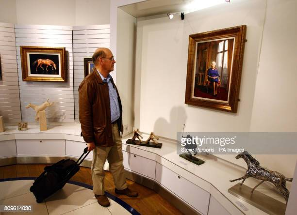 Passenger Roger Andrews looks at a portrait of HM Queen Elizabeth II which is being displayed at the EXPO Fine Art gallery in the Departures area of...