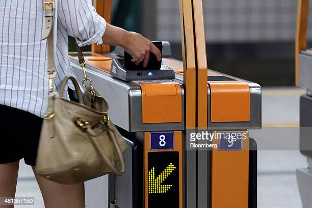 A passenger scans a wallet containing a Tmoney transportation card at a fare gate inside the Gwanghwamun subway station in Seoul South Korea on...
