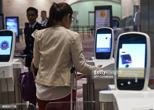 A passenger scans her thumb on an automated immigration gate at the newlyopened Changi International Airport's Terminal 4 in Singapore on October 31...