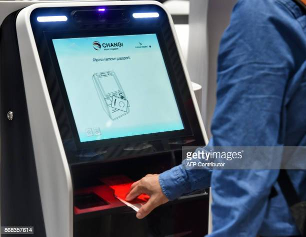 A passenger scans his passport to checkin luggage at an automated booth at the newlyopened Changi International Airport's Terminal 4 in Singapore on...