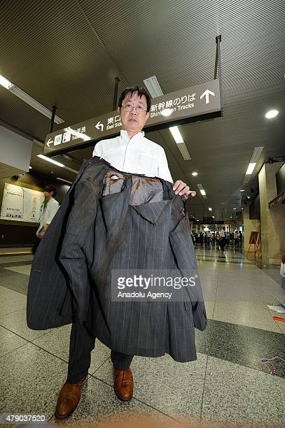 A passenger shows his burnt jacket while trying to exit the Shinkansen after a 71yearold man set himself alight on a Japanese bullet train killing...