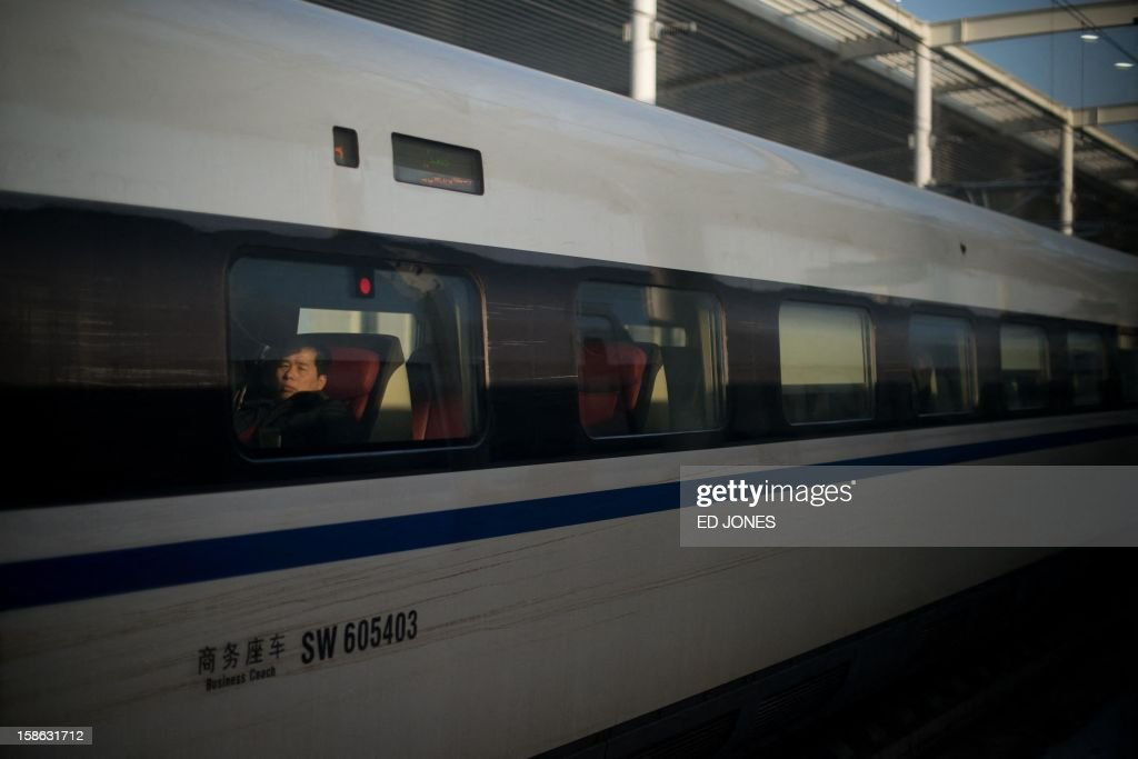 A passenger sits aboard a high-speed train at the Beijing West Railway Station in Beijing on December 22, 2012. China showed off the final link of the world's longest high-speed rail route, set to open on December 26, stretching from Beijing to the southern Chinese city of Guangzhou. Travelling at around 300 kph, trains on the new route are expected to cover the 2,298-kilometre (1,425-mile) journey in a third of the current time from 22 hours to eight. AFP PHOTO / Ed Jones