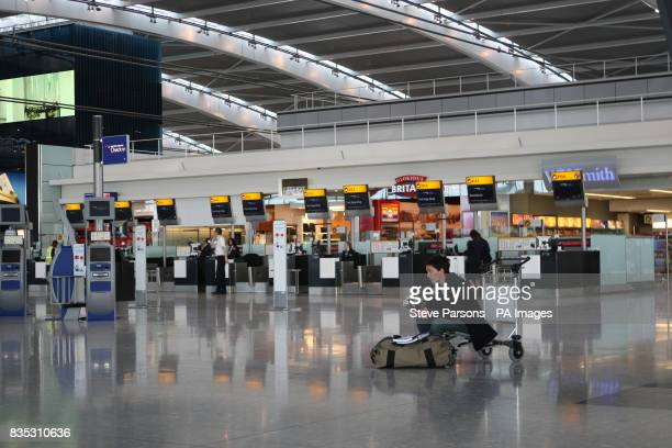 A passenger sits and waits on a trolley in departures of Terminal 5 at Heathrow Airport Middlesex