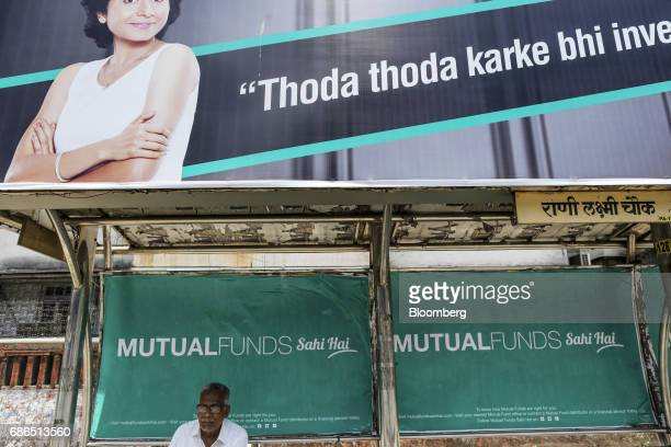 A passenger sits below an advertisement for the Mutual Funds Sahi Hai campaign by the Association of Mutual Funds in India at a bus stop in Mumbai...