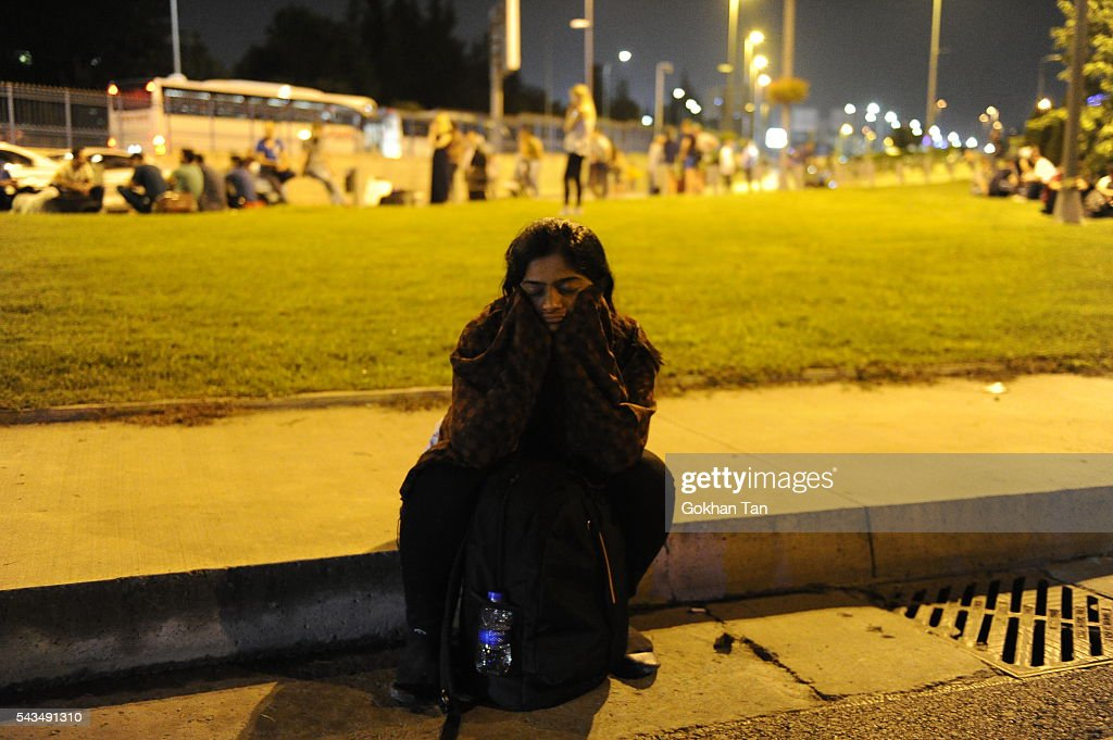 A passenger sits dejectedly outside the Turkey's largest airport, Istanbul Ataturk after the suicide bomb attacks, June 28, 2016, Turkey. Three suicide bombers opened fire before blowing themselves up at the entrance to the main international airport in Istanbul, killing at least 28 people and wounding at least 60 people according to Istanbul governor Vasip Sahin.
