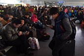 A passenger sits on his bag while waiting to board a train at Beijing West Railway Station on February 13 2015 Millions of Chinese are making...