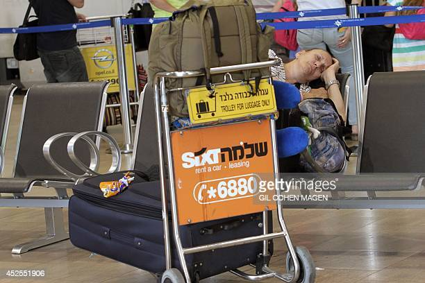 A passenger sleeps on a seat in the departure lounge of Ben Gurion International airport near Tel Aviv following several flight cancellations on July...