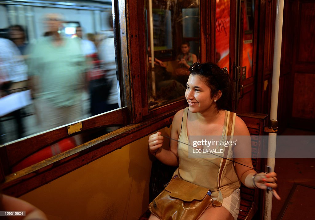 A passenger smiles while on board of one of the Le Burgeoise wagons of the A Line subway, in Buenos Aires, on January 11, 2013 during the so called last ride of the historic trains. The Line A will be closed betwen January 12 and March 8 following a decision by Buenos Aires city Mayor Mauricio Macri to replace the fleet with Chinese-made wagons. Line A was the first subway line to work in the southern hemisphere and its trains are among the ten oldest still working daily. The La Brugeoise wagons were constructed between 1912 and 1919 by La Brugeoise et Nicaise et Delcuve in Belgium. AFP PHOTO/Leo La Valle