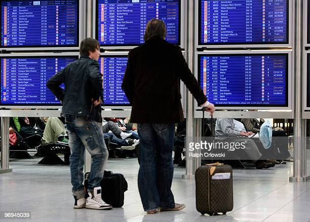 Passenger stand in front of a flight schedule board at the Terminal 1 of Frankfurt International Airport on February 22 2010 in Frankfurt am Main...