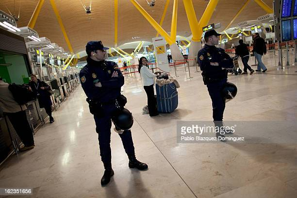 A passenger stands behind a police cordon during a protest of Spanish Airline Iberia staff against job cuts at Barajas Airport on February 22 2013 in...