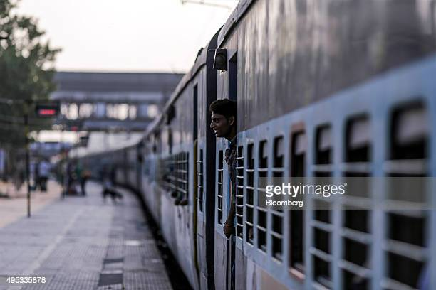 A passenger stands in a carriage doorway on the Kalka Mail train as it stands at Mughalsarai Junction station in Mughalsarai Uttar Pradesh India on...