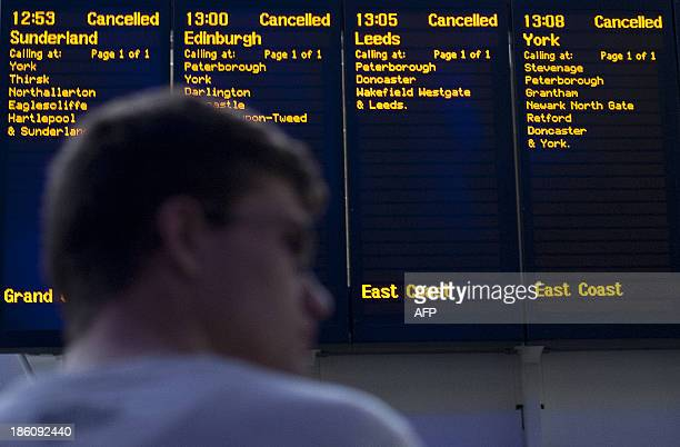 A passenger stands in front of the destination boards showing cancelled trains at Kings Cross train station on October 28 following a strong storm...