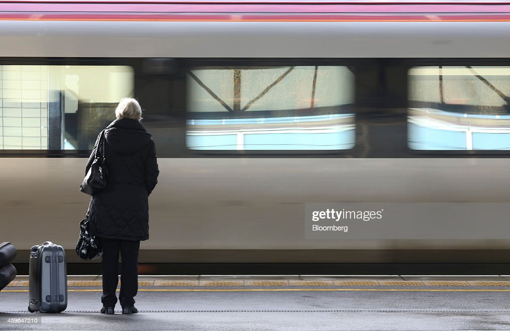 A passenger stands on a railway platform as a West Coast train, operated by Virgin Trains, arrives at at Milton Keynes railway station in Milton Keynes, U.K., on Thursday, Nov. 27, 2014. Virgin Trains and partner Stagecoach Group Plc were chosen to run the London-Edinburgh rail route, fending off rival bids from FirstGroup Plc and Eurostar International Ltd. and delivering a boost for Richard Branson a month after the fatal crash involving his space venture. Photographer: Chris Ratcliffe/Bloomberg via Getty Images