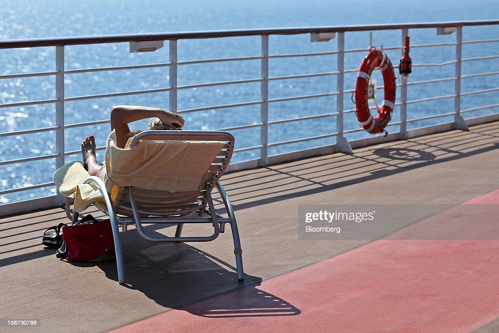 A passenger sunbathes on a lounge chair aboard Celebrity Cruises Inc.'s Constellation cruise ship in the Caribbean Sea near the coast of Cuba on Wednesday, Dec. 19, 2012. Royal Caribbean Cruises Ltd. operates Azamara Club Cruises, Celebrity Cruises, CDF Croisieres de France, Pullmantur Cruises and Royal Caribbean International. Photographer: Tim Boyle/Bloomberg via Getty Images