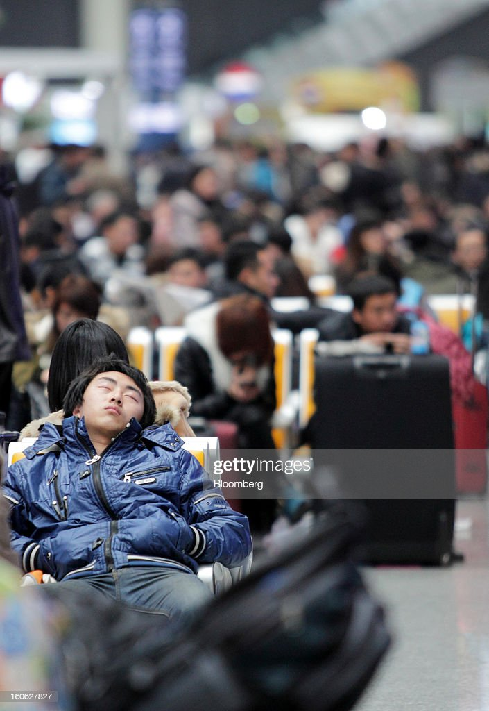 A passenger takes a nap as he waits to board his train at Hongqiao Railway Station in Shanghai, China, on Sunday, Feb. 3, 2013. Forecasts of snow and rain across China threaten to disrupt the travel plans of millions of Chinese heading home for the Lunar New Year holidays that start Feb. 9, the national weather agency warned. Photographer: Tomohiro Ohsumi/Bloomberg via Getty Images