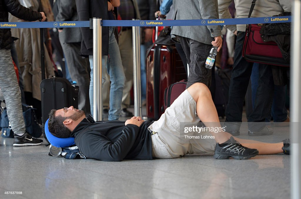 A passenger takes a nap as other passengers wait in line for Lufthansa flights on October 20 2014 in Frankfurt am Main Germany Vereinigung Cockpit...