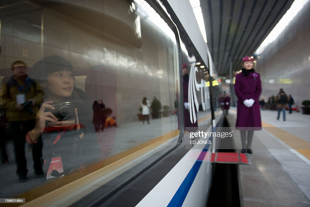 A passenger takes photos from a window of a high-speed train at the Beijing West Railway Station in Beijing on December 22, 2012. China showed off the final link of the world's longest high-speed rail route, set to open on December 26, stretching from Beijing to the southern Chinese city of Guangzhou. Travelling at around 300 kph, trains on the new route are expected to cover the 2,298-kilometre (1,425-mile) journey in a third of the current time from 22 hours to eight. AFP PHOTO / Ed Jones