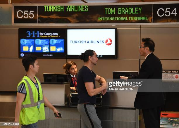 A passenger talks with a Turkish Airlines manager beside a checkin counter at Los Angeles International Airport in Los Angeles California on March 21...
