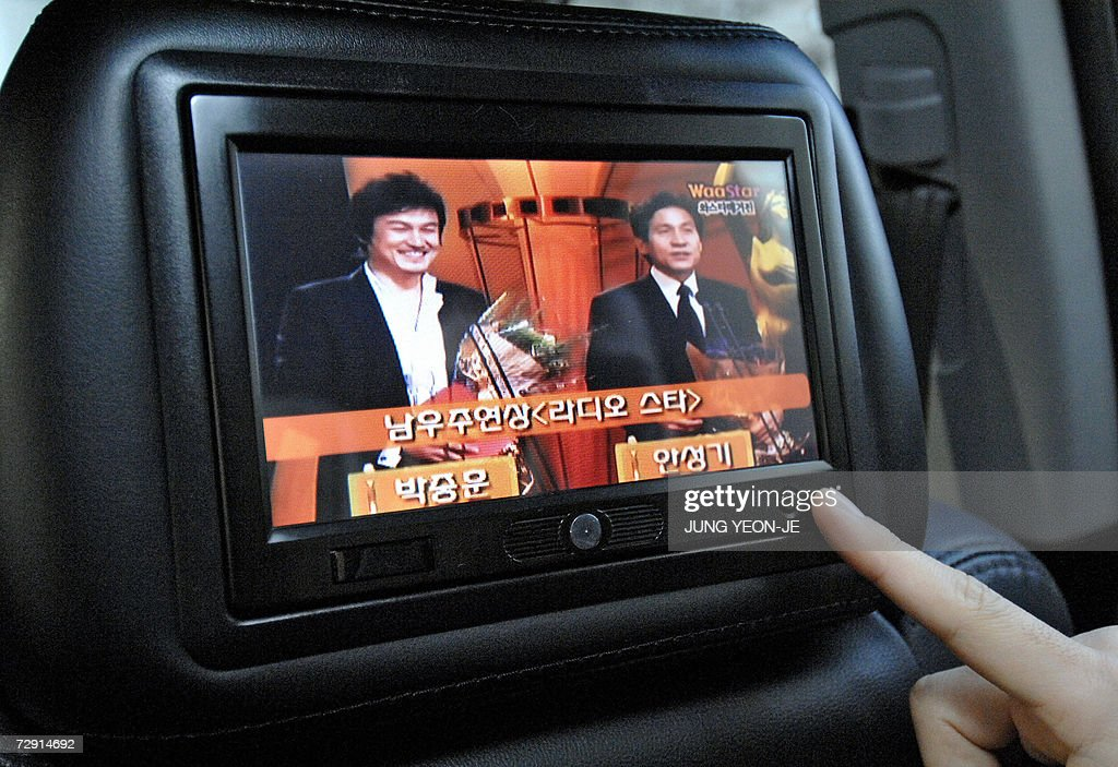 A passenger touches a liquid crystal display screen situated in the back of the headrest on the front passenger seat in a taxi showing advertisements...