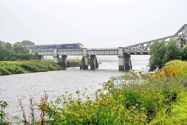Passenger train crossing railway bridge over estuary river
