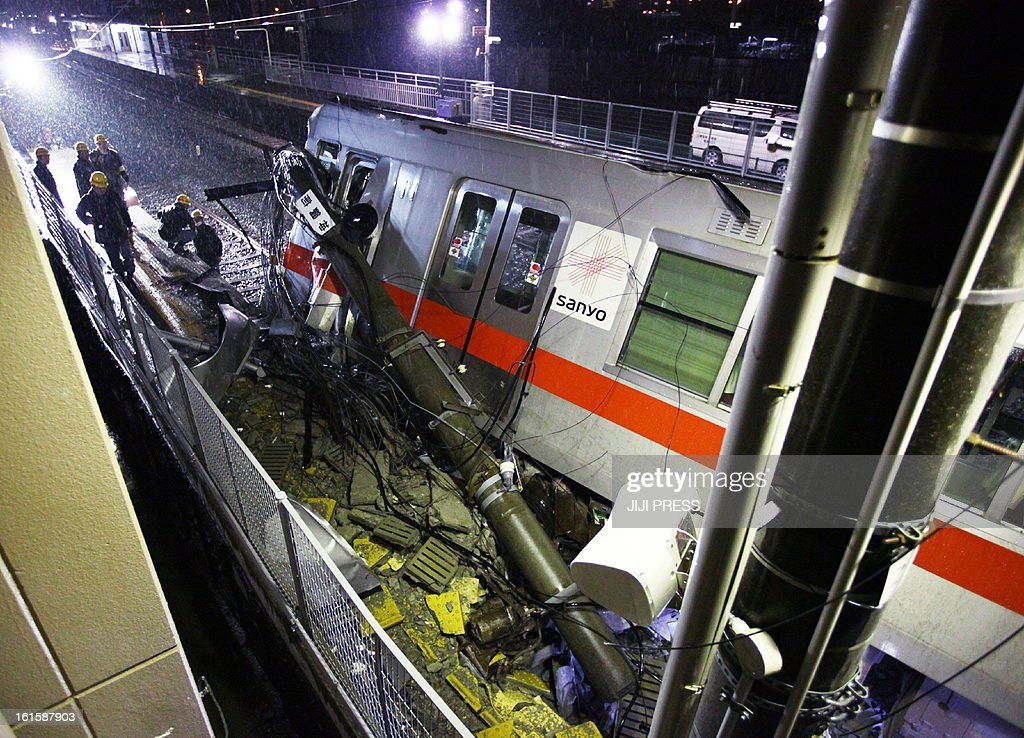 A passenger train of the Sanyo Electric Railway is derailed after the train hit a truck at a level crossing in Takasago city in Hyogo prefecture, western Japan on February 12, 2013. An express passenger train hit a truck at a level crossing in Japan on February 12, police said, with footage and reports from the scene showing it had mounted a station platform.