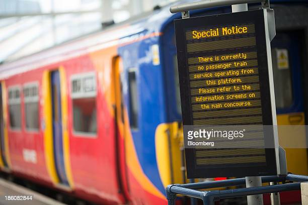 A passenger train operated by South West Trains Ltd sits on a platform as an electronic board displays service disruption information at Waterloo...
