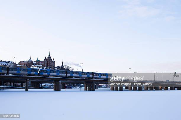 Passenger train passing through bridge over frozen lake