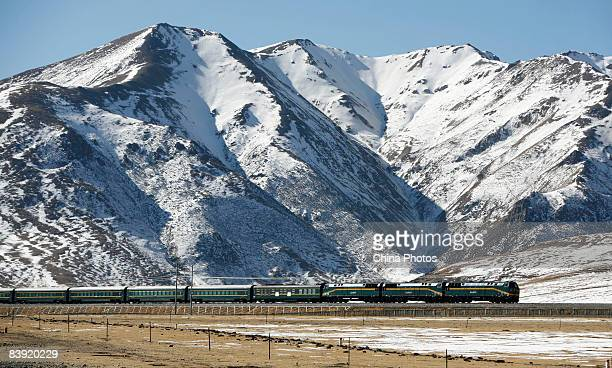 A passenger train runs past a snowcapped mountain on December 4 2008 in Damxung County of Tibet Autonomous Region China The 1956km QinghaiTibet...