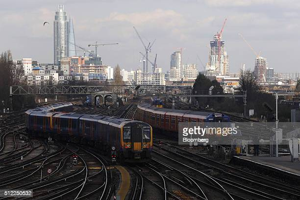 Passenger trains move in and out of Clapham Junction railway station as construction cranes sit on the skyline beyond in London UK on Wednesday Feb...