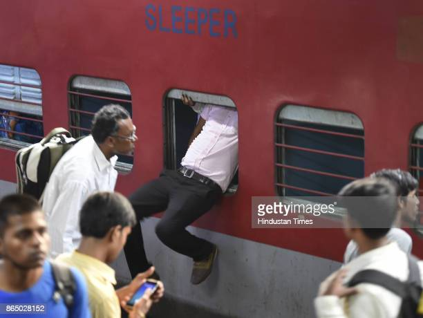 A passenger tries to enter from the emergency window of 12394 Sampoorn Kranti Express train which runs from New Delhi to Patna who wanted to go to...