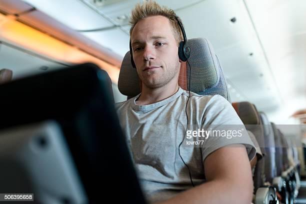 Passagier schreiben und hören am laptop im Flugzeug