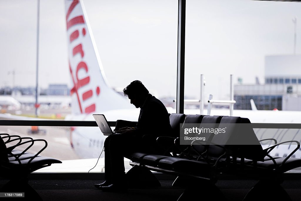 A passenger uses a laptop computer as an aircraft operated by Virgin Australia Holdings Ltd. stands outside a gate at the domestic terminal of Sydney Airport in Sydney, Australia, on Thursday, Aug. 29, 2013. Virgin will make a net loss in the range of A$95 million to A$110 million when it reports annual results tomorrow, the Brisbane-based carrier forecast Aug. 5. Photographer: Ian Waldie/Bloomberg via Getty Images