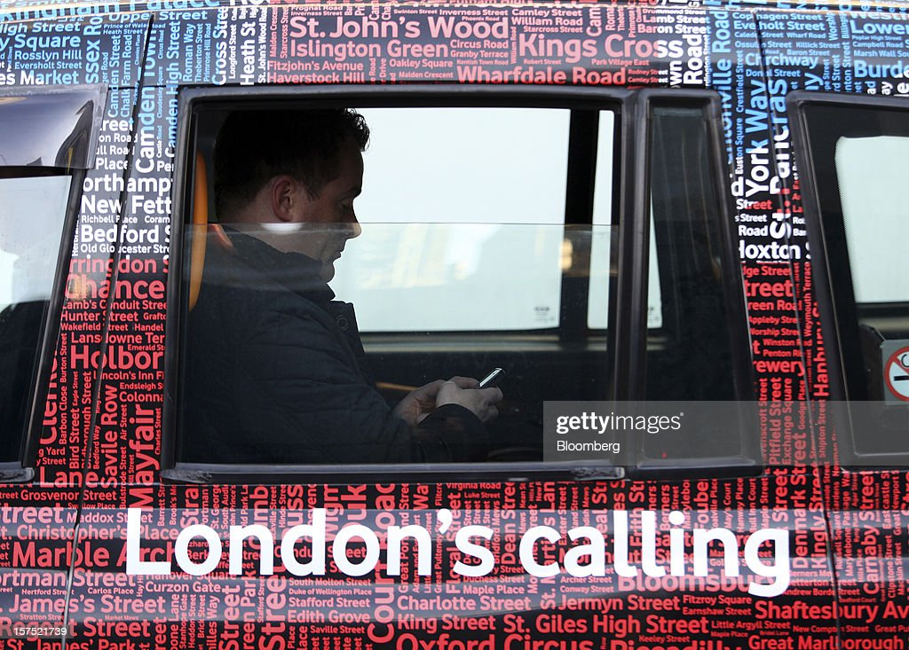 A passenger uses a mobile phone as he travels inside a London taxi, bearing a Vodafone Group Plc advert, in London, U.K., on Friday, Nov. 30, 2012. U.K. banks have become more unwilling to finance development projects without a tenant committed to lease space or a buyer for the completed property. Photographer: Chris Ratcliffe/Bloomberg via Getty Images