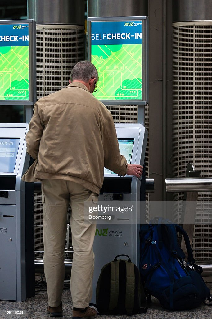 A passenger uses an automatic check-in machine at Lisbon International (Portela) airport, operated by ANA-Aeroportos de Portugal SA, in Lisbon, Portugal, on Tuesday, Jan. 8, 2013. Portugal's government agreed to sell state-owned airport operator ANA-Aeroportos de Portugal SA to Vinci SA for 3.08 billion euros ($4.07 billion), raising money for the debt-strapped country. Photographer: Mario Proenca/Bloomberg via Getty Images