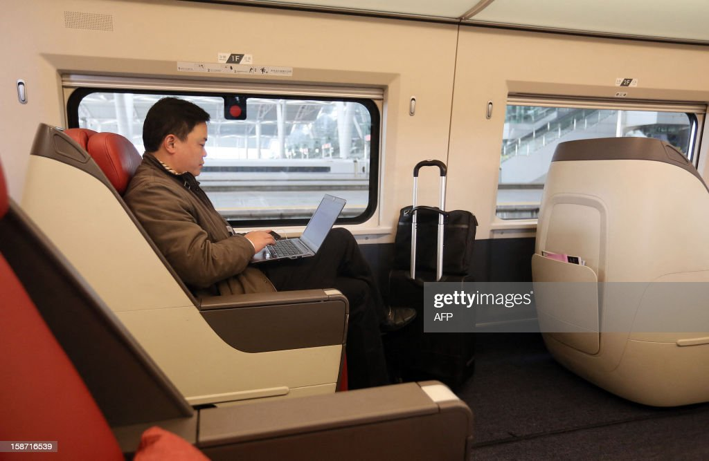 A passenger uses his computer on the new 2,298-kilometre (1,425-mile) line between Beijing and Guangzhou in Guangzhou, south China's Guangdong province on December 26, 2012. China started service on December 26 on the world's longest high-speed rail route, the latest milestone in the country's rapid and -- sometimes troubled -- super fast rail network. The opening of this new line means passengers will be whisked from the capital to the southern commercial hub in just eight hours, compared with the 22 hours previously required. CHINA