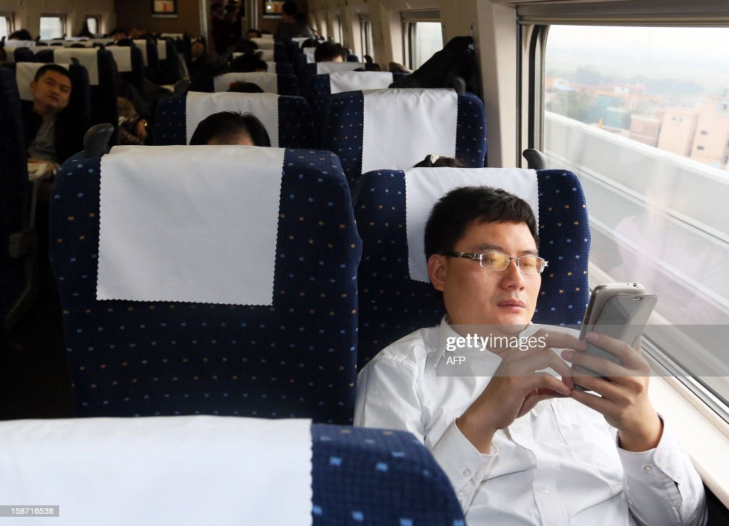 A passenger uses his mobile phone on the new 2,298-kilometre (1,425-mile) line between Beijing and Guangzhou in Guangzhou, south China's Guangdong province on December 26, 2012. China started service on December 26 on the world's longest high-speed rail route, the latest milestone in the country's rapid and -- sometimes troubled -- super fast rail network. The opening of this new line means passengers will be whisked from the capital to the southern commercial hub in just eight hours, compared with the 22 hours previously required. CHINA