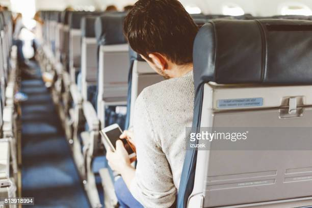 Passagier met behulp van mobiele telefoon tijdens vlucht