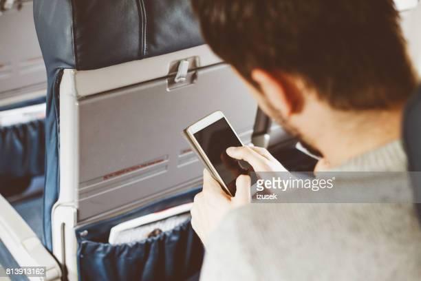 Passagier met behulp van slimme telefoon terwijl het reizen per vliegtuig