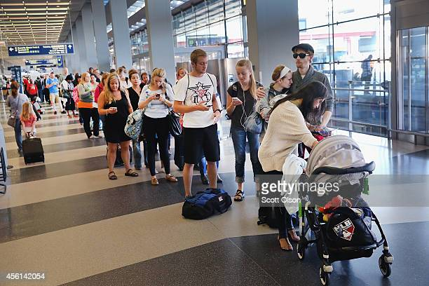 Passenger wait in line to reschedule flights at O'Hare International Airport on September 26 2014 in Chicago Illinois All flights in and out of...