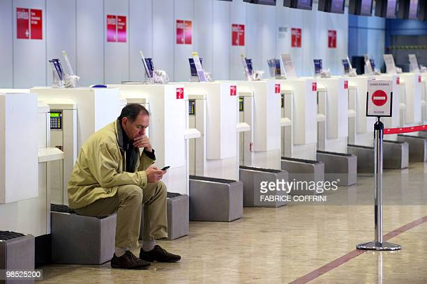 A passenger waits at Geneva's International Airport on April 18 2010 as planes are grounded as a result of the volcanic eruption in Iceland...