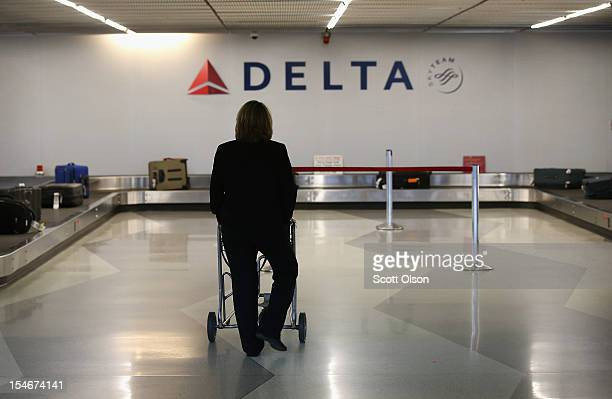 A passenger waits for her luggage in the Delta baggage claim at O'Hare International Airport on October 24 2012 in Chicago Illinois Delta Airlines...