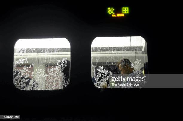 A passenger waits in the coach of the derailed Komachi 25 Akita Shinkansen bullet train on March 2 2013 in Omagari Akita Japan Passengers were stuck...