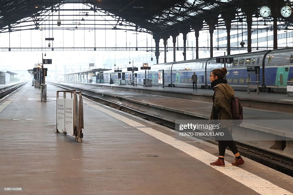 A passenger waits on June 1, 2016 at the Gare de Lyon railway station in Paris, at the start of a strike by employees of French state-owned rail operator SNCF to protest against government labour reforms. Rail strikes in France are expected to take full effect, disrupting transport across the country just over a week before the Euro 2016 football championship starts. / AFP / KENZO