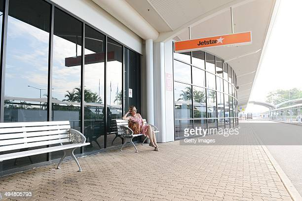 A passenger waits outside of Darwin airport on May 31 2014 in Darwin Australia Flights in and out of Darwin have been suspended as volcanic ash from...